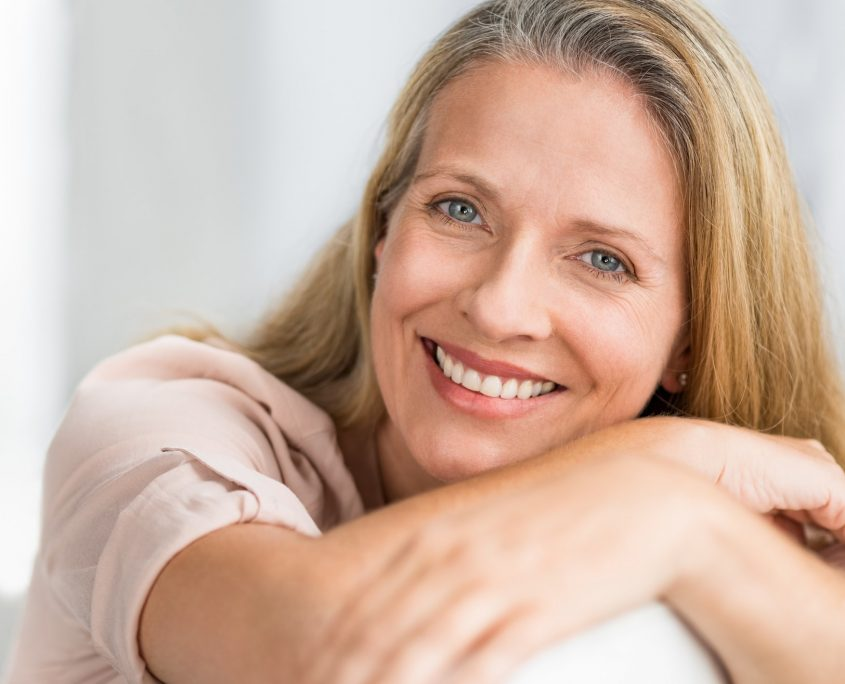 smiling woman on couch O2dental Invisalign Vancouver