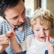0ral hygiene father brushing his teeth with-a-toddler boy O2Dental Vancouver